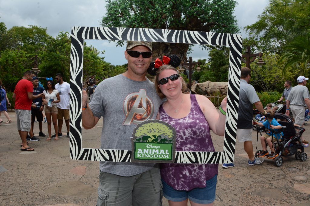 "Husband and wife holding ""Animal Kingdom"" sign in front of the Tree of Life in Animal Kingdom"