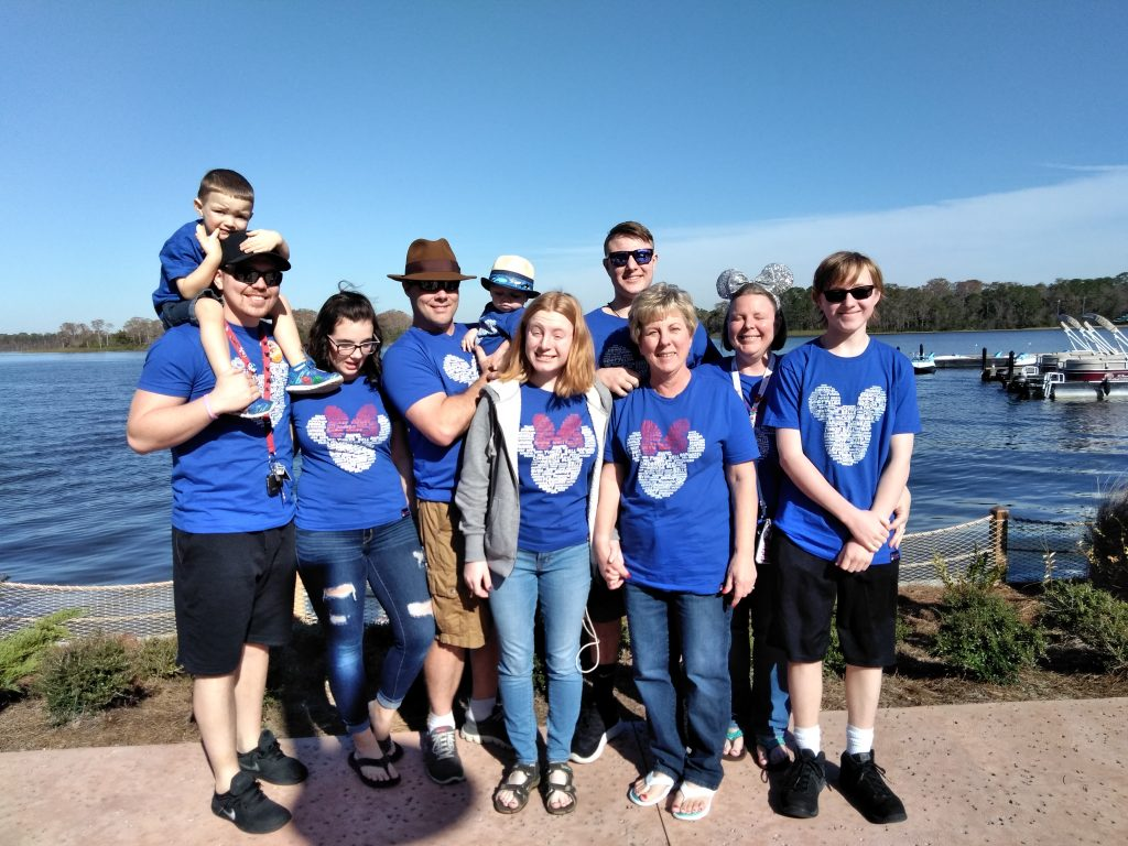 Family of four generations in matching shirts overlooking a body of water