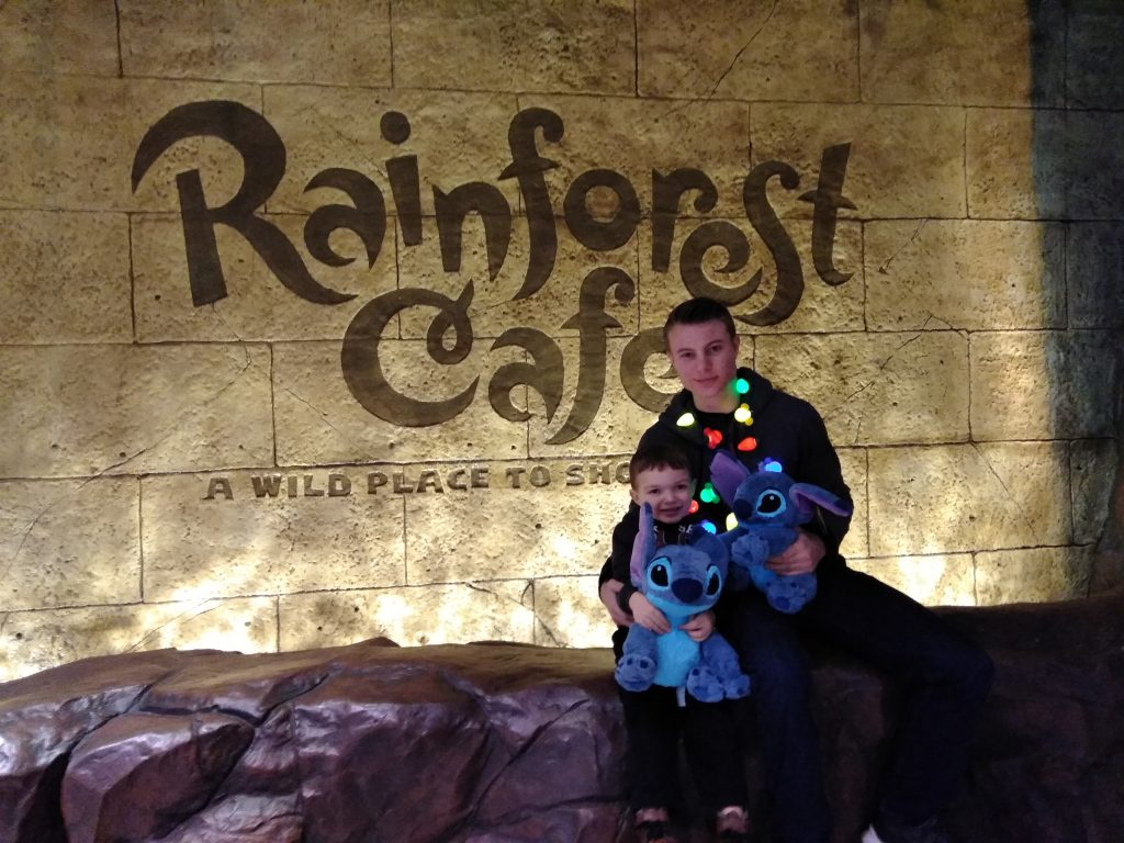 Nephew and uncle wearing Christmas necklaces and holding Stitch stuffed toys outside of Rainforest Cafe