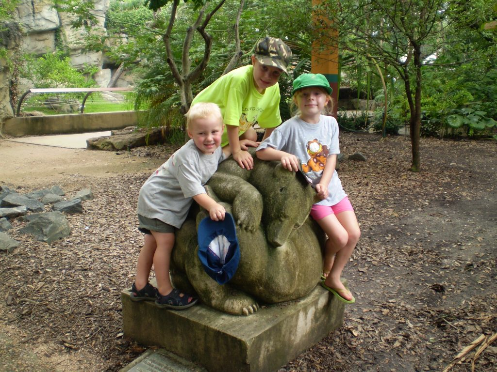 Three young children with statue at the zoo