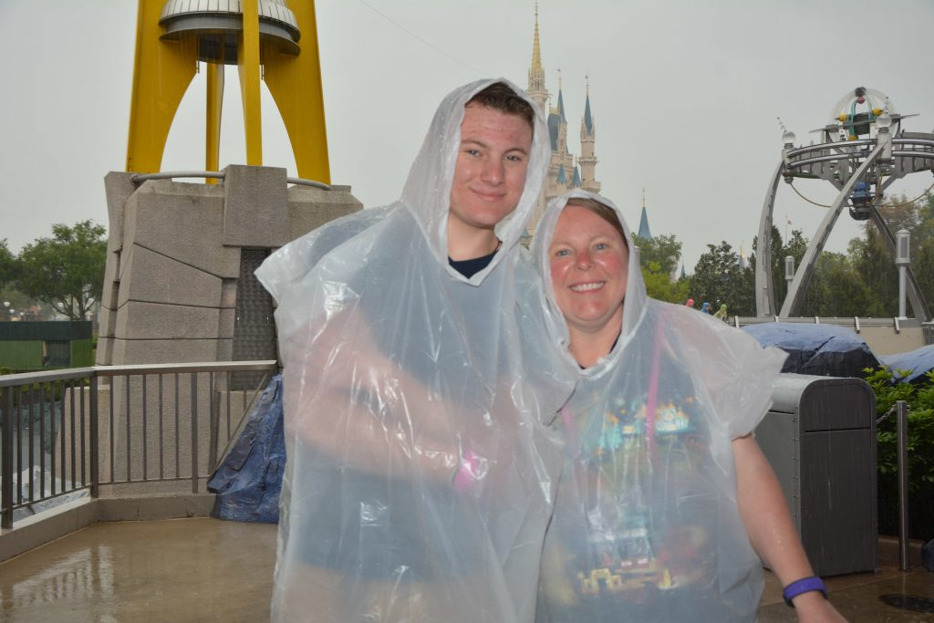 Mom and son in ponchos on a rainy day in Walt Disney World's Magic Kingdom