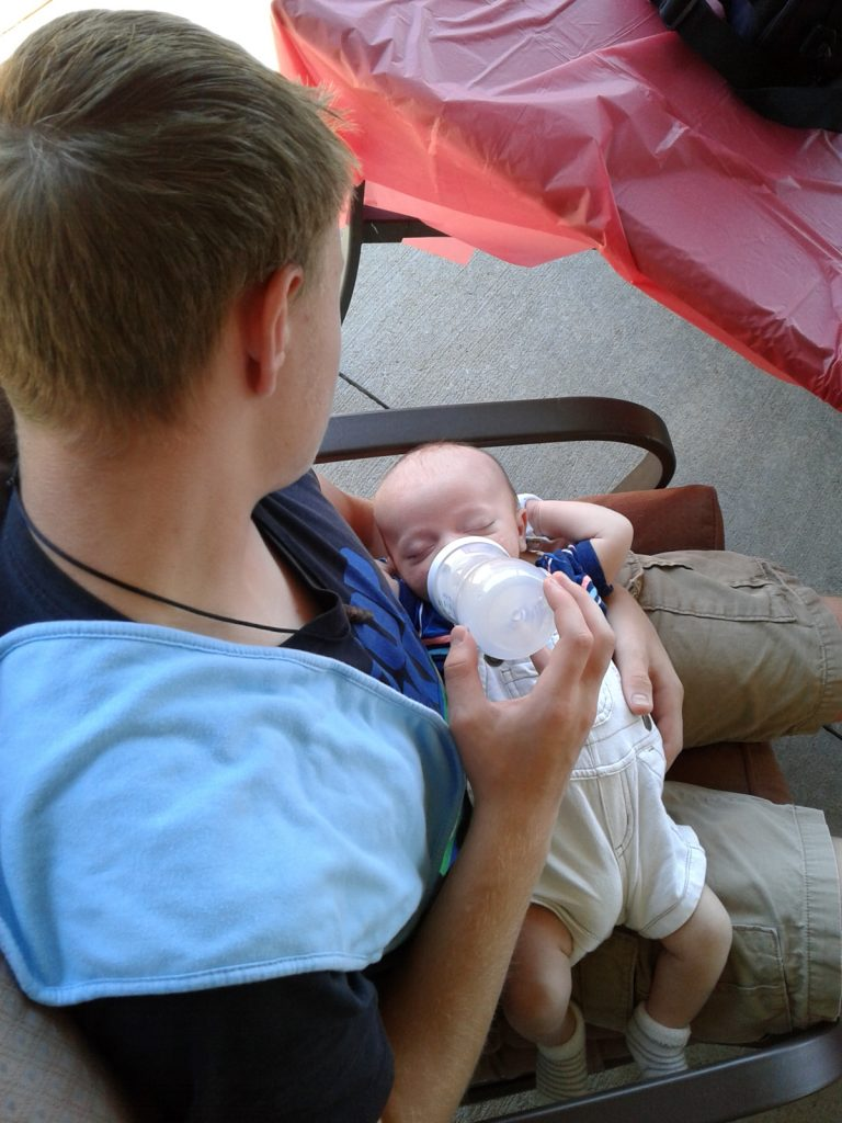 Teen uncle feeding baby with bottle