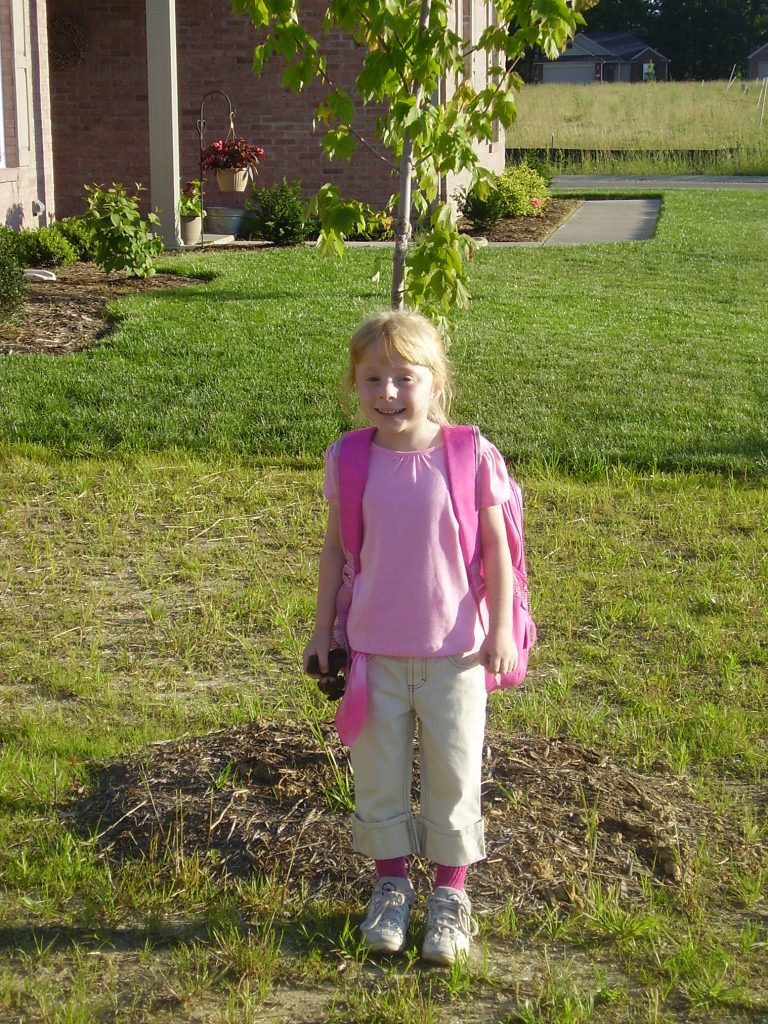 Young girl standing in front of young tree