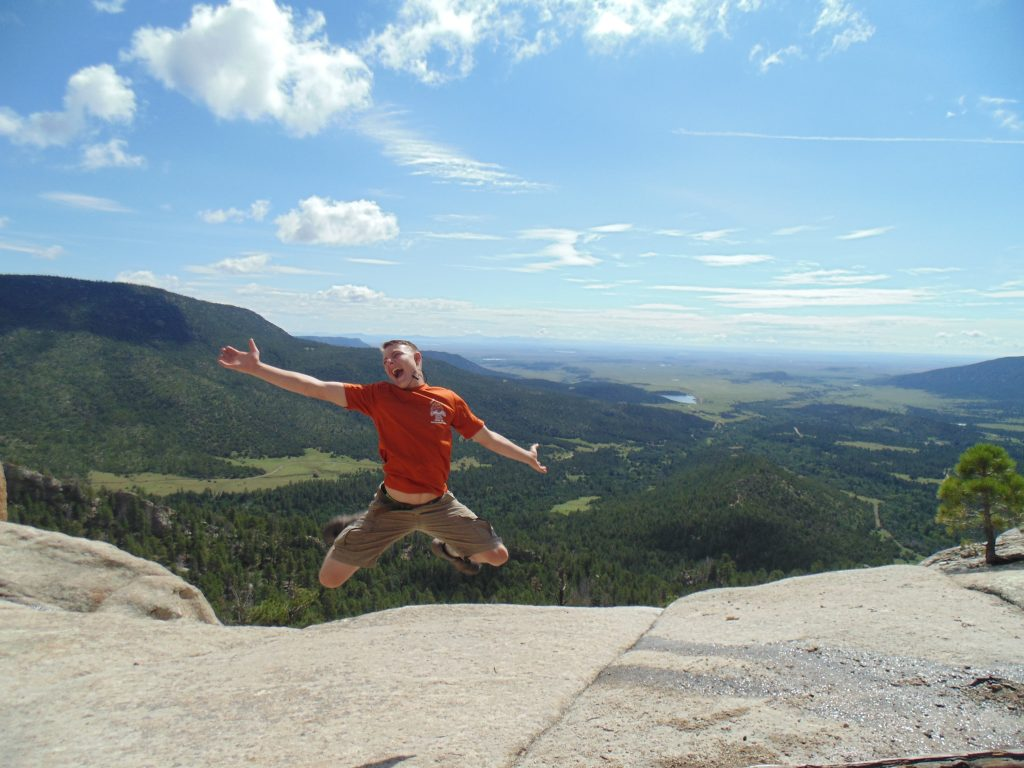 Teen boy on mountain top with blue sky in background jumping with excitement