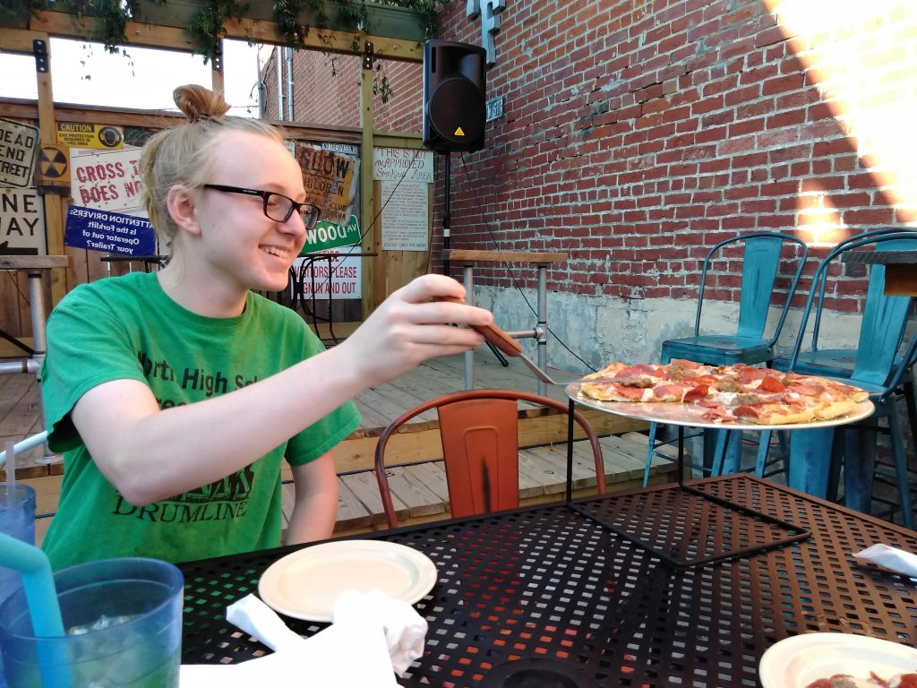Franklin Street Pizza Factory boy with pizza on outside patio