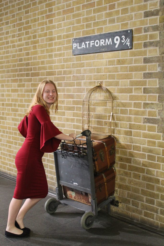 Teen girl at platform 9 3/4 in London, England