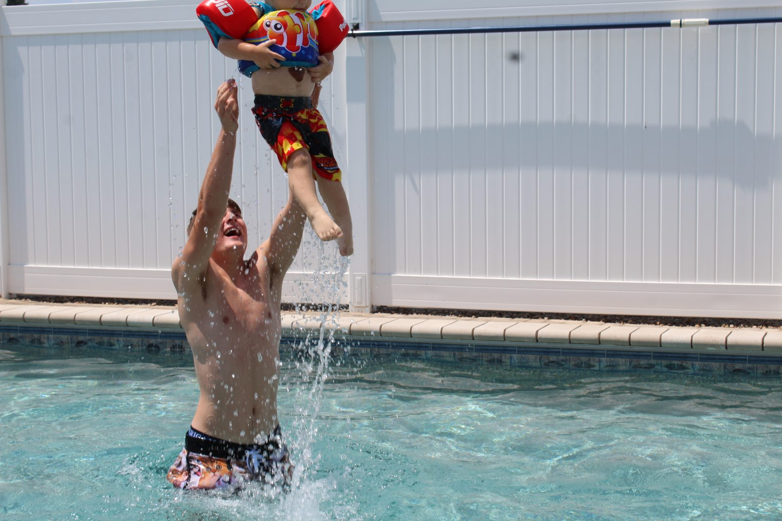 Teen uncle and toddler in pool